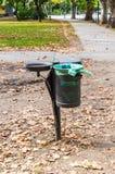 Metal el bote de basura en el parque en otoño Foto de archivo libre de regalías