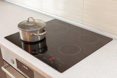 Metal el cazo de acero en cocina moderna con la estufa de la inducción Foto de archivo libre de regalías