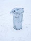 Metal el cubo de la basura con la tapa cerrada en la nieve Imágenes de archivo libres de regalías