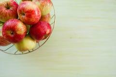 Metal el cuenco con las manzanas verdes, amarillas y rojas en la esquina superior izquierda en el fondo de madera verde Foto de archivo libre de regalías