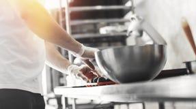 Metal el cuenco y las manos que cocinan los caramelos de chocolate en la tabla del metal imagen de archivo libre de regalías