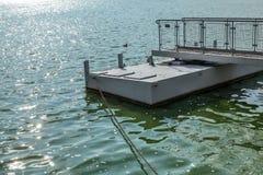 Metal el embarcadero del barco, en un lago verde del agua, sol que chispea en pequeño w imagen de archivo