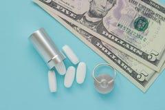 Metal el envase para las píldoras y el dinero en un fondo azul, concepto de drogas costosas, primer imagen de archivo