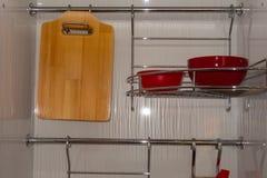Metal el estante para los platos y a una tabla de cortar de madera a partir de dos secciones Imagenes de archivo