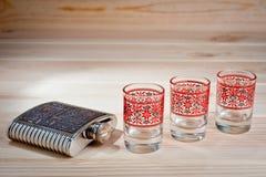 Metal el frasco para las bebidas alcohólicas y tres vidrios en un fondo de madera fotos de archivo