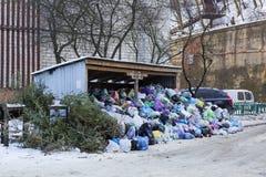 Metal el hangar y los cubos de la basura cubiertos de la basura grande del montón Fotografía de archivo libre de regalías