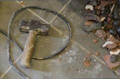 Metal el martillo de trineo en piso tejado con los fragmentos del hormigón Imagen de archivo