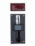 Metal el panel de la ranura de moneda de una máquina de fichas con las ranuras de la entrada y de la salida y abotone en un fondo Foto de archivo libre de regalías