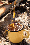 Metal el primer de la taza con el chapoteo del café caliente en el fondo de la hoguera Foto de archivo