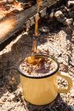 Metal el primer de la taza con el chapoteo del café caliente en el fondo de la hoguera Imagen de archivo