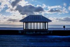 Metal el refugio del asiento, playa de Seaford, perro que camina del hombre solitario Foto de archivo libre de regalías