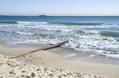 Metal el tubo del conducto en la playa al mar imágenes de archivo libres de regalías