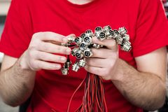 Four pin connectors with thread in hand. Metal electric four pin connectors in male hands stock image