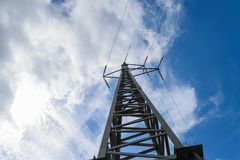 Metal electricity pole in blue sky with white clouds background.  Stock Photography