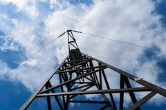 Metal electricity pole in blue sky with white clouds background.  Stock Image
