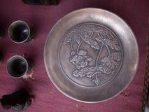 Metal embossed fruit plate. A metal embossed fruit bowl for fruit ceremonies is engraved with lotus flowers stock images