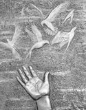 Metal engraving of hand with flying doves. Close up detail of a metallic sculpture in memory of the Liverpool Hillsborough victims Royalty Free Stock Images