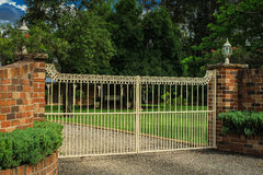 Metal entrance gates set in brick fence. Wrought iron driveway entrance gates set in brick fence Stock Image