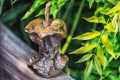 Metal a escultura do núcleo da maçã com as folhas verdes no fundo Fotos de Stock