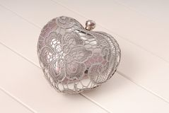 Metal evening handbag, clutch has heart shape, handbag is on whi. Te background, sparkly, silvery grey handbag Royalty Free Stock Image