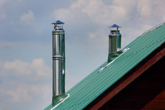 Metal exhaust pipe on the green metal roof Royalty Free Stock Images