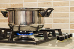 Metal faire cuire le bac restant sur le poêle de cuisine avec la flamme image libre de droits