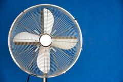 Metal fan. A metal fan on a blue background Stock Image