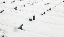 Metal fasteners. For wooden benches under the snow, winter in the old stadium, in need of reconstruction stock image