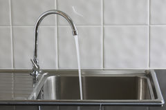 Metal faucet in a kitchen is open water Royalty Free Stock Image