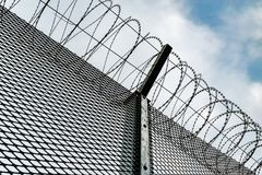 Metal fence with barbed wire. stock image