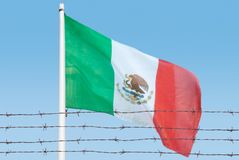 Flag of wires. Metal fence with barbed wire on a Mexican flag. Separation concept, borders protection.Social issues on refugees or illegal immigrants royalty free stock photo