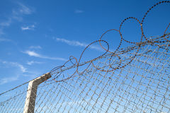 Metal fence with barbed wire over blue sky Royalty Free Stock Photos