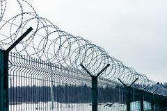 Metal fence with barbed wire on top against the sky royalty free stock photography