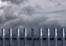 Metal fence with dark clouds. Metal fence with stormy dark clouds and sunlight stock image