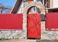 Metal Fence Door with red wild stone. Metal fencing exterior with door bell and postbox. stock image