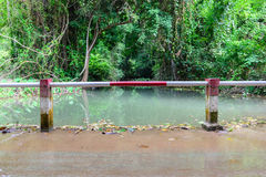 Metal fence for flooding over the road at national park waterfall Stock Photography