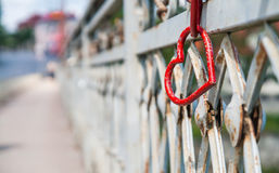 Metal fence hanging red heart lock. On a metal fence hanging red heart lock royalty free stock photo