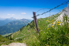 Metal fence on mountain meadow Royalty Free Stock Photography