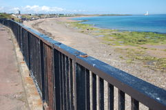 Metal fence on the promenade at Whitley Bay. Fence on the lower prom at Whitley Bay with St Mary's lighthouse in the distance Royalty Free Stock Photo