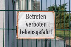 Warning sign on a fence with the german words - Do not enter - Danger to life! royalty free stock photography