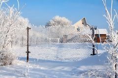 Fence from square grid in white fluffy hoarfrost stock photo