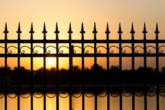 Metal fence at sunset Stock Photo