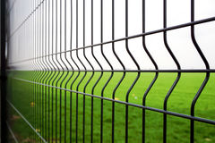 Metal fence wire. Grass and sky in the background Stock Image