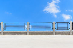 Metal fences on cement road with clouds Royalty Free Stock Photos