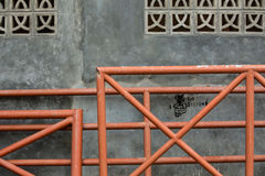 Metal fenches on the wall. Orange metal fenches on cracked cement wall Royalty Free Stock Photography
