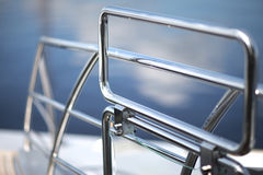 Metal fencing. Shiny chrome metal fencing and railings yacht on the background of the smooth surface of the water Stock Photos