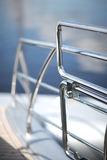 Metal fencing. Shiny chrome metal fencing and railings yacht on the background of the smooth surface of the water Royalty Free Stock Images