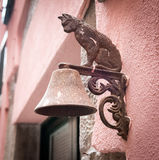 Metal figure of cat as decoration of bell carried on a wall.  Royalty Free Stock Image