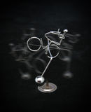 Metal figure riding a bicycle Stock Photo