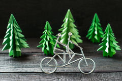 Metal figures cyclists and spruce origami Stock Photography